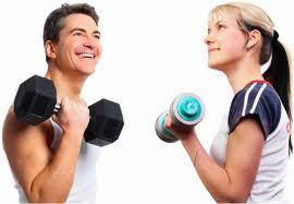 dos personas sonrientes haciendo una flexión de codo, con mancuerna en mano